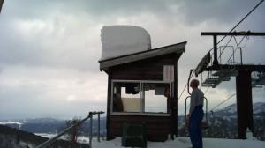 雪が落ちた屋根の様子を見るおじさん