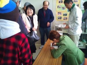 モンキー高野さん販売DVDにサインをされている様子